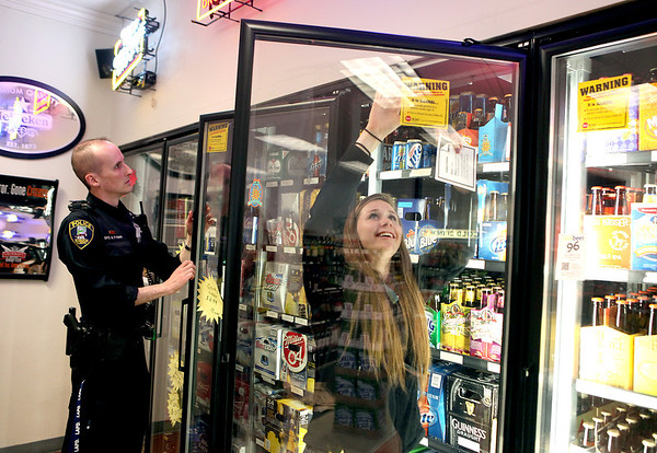 "St. Charles East junior Clara Stoffel posts a notice to deter underage drinking at J & S Liquor in St. Charles as St. Charles Police Officer Bill Tynan looks on. Students from both St. Charles East and St. Charles North, along with officers, canvassed the city as part of ""Project Sticker Shock"" for the fourth consecutive year."