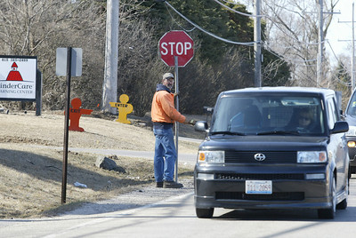 H. Rick Bamman - hbamman@shawmedia.com McHenry public works crew member David Christopher slows traffic along Crystal Lake Ave in McHenry.