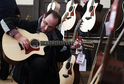 Sarah Nader - snader@shawmedia.com Eliot Levy of Lake in the Hills tries out a Taylor Guitar while attending the Taylor Guitars Road Show at The Old Towne Hall in Crystal Lake on Tuesday, April 16, 2013. The event was sponsored by The Player's Bench Music Store and featured guitar information and demos with a team from the Taylor factory.