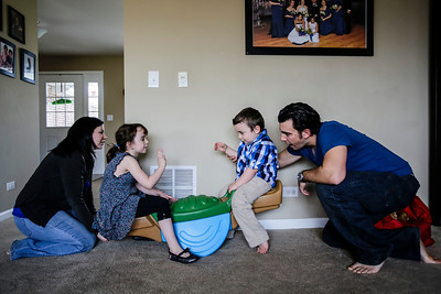 Lathan Goumas - lgoumas@shawmedia.com Julia Fresso (far left) and Joe Fresso (far right) play with their children Chloe Gast, 6, and Mason Fresson, 4, at the family's Lake in the Hills, Ill. home on Wednesday, April 24, 2013. Mason was diagnosed autistic at age one and the family is attempting to raise money for an autism assistance dog to help him