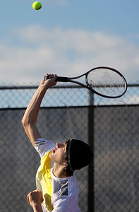 Sarah Nader - snader@shawmedia.com Jacobs' Michael Bujacz serves while competing in a doubles match against Prairie Ridge in Algonquin on Wednesday, April 24, 2013.