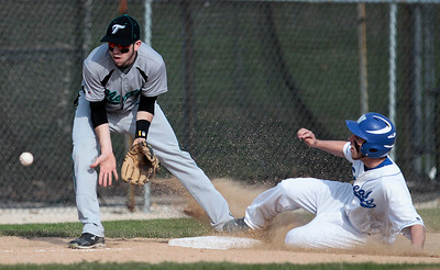 Kyle Grillot - kgrillot@shawmedia.com   Woodstock senior Andy Buhrow slides into third base as Woodstock North junior Jake Schnulle errors during the third inning against Woodstock North at Emricson Park on Friday, April 26, 2013.