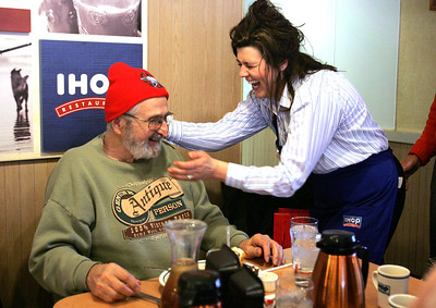"Monica Maschak - mmaschak@shawmedia.com IHOP waitress Christine Schaefer laughs with Russ Nolte, a 1951 Crystal Lake Community High School alum, as she presents him with a ""Lunch Hero"" hat, made by another group member. About 30 alumnus gathered at the McHenry IHOP on Thursday, April 11, 2013 to celebrate their 100th lunch-time meeting since 2004. Shaefer has been the same waitress for the group since their first meeting."