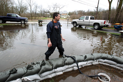 Sarah Nader - snader@shawmedia.com Rick Michelsen of McHenry helps a friends place sandbags around their home on W Riverside Drive in McHenry on Thursday, April 19, 2013.
