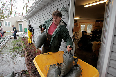 Sarah Nader - snader@shawmedia.com Mike Domann of McHenry helps his neighbor lay down sandbags around his home on W Riverside Drive in McHenry on Thursday, April 19, 2013.