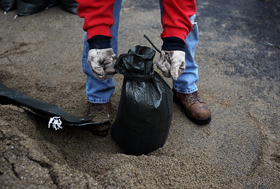 Sarah Nader - snader@shawmedia.com Mike Snudson of Elgin ties sandbags while helping a friend deal with his flooded yard on Thursday, April 19m 2013.