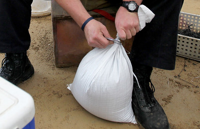 Monica Maschak - mmaschak@shawmedia.com Volunteer Rich Hoehne, from the Fox Lake Fire Protection District,  ties off filled sand bags at the Fox Lake Street Department on Thursday, April 18, 2013. Volunteers estimated to have filled more than 12,000 sand bags.