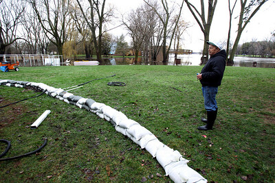 Sarah Nader - snader@shawmedia.com Bill Kusch of McHenry looks at his home in McHenry on Thursday, April 19, 2013. Flood water covered most of his front yard.