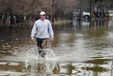 Sarah Nader - snader@shawmedia.com Mike Kalter of McHenry walks in knee high water on W Riverside Drive after helping his neighbor fill sandbags on Thursday, April 19, 2013.