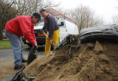Sarah Nader - snader@shawmedia.com Mike Knudson (left) of Elgin and Ken Kusch of Roselle fill sandbags at Kusch's fathers house on W Riverside Drive in McHenry after the Fox River behind his house flooded on Thursday, April 19, 2013.