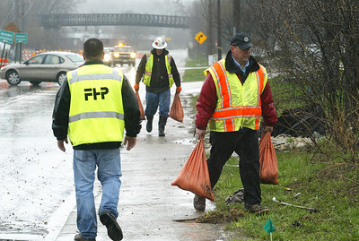 H. Rick Bamman - hbamman@shawmedia.com Workers move sandbags to slow the flow of water coming from a retention pond across the street from the Algonquin Post Office. The water and mud closed Algonquin Rd.for much of the morning Thursday, April 18, 2013 in Algonquin.