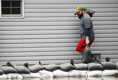 Sarah Nader - snader@shawmedia.com Aaron Dullum of McHenry places sandbags around his grandfathers home on W Riverside Drive in McHenry after the Fox River flooded most of the yard on Thursday, April 19, 2013.