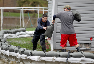Sarah Nader - snader@shawmedia.com Rick Michelsen (left) of McHenry and Aaron Dullum of McHenry place sandbags around Dullum's grandfathers home on W Riverside Drive in McHenry on Thursday, April 19, 2013.