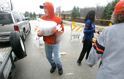 H. Rick Bamman - hbamman@shawmedia.com LaFox River Drive resident Patrick Headtke with neighbors load sandbags onto a trailer Thursday, April 18, 2013 in Algonquin.