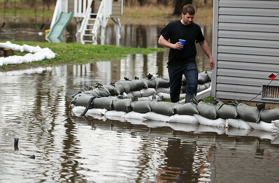 Sarah Nader - snader@shawmedia.com Corbin Turner of Genoa walks around his grandfathers home on W Riverside Drive in McHenry while helping to control the water after the Fox River flooded most of the yard on Thursday, April 19, 2013.