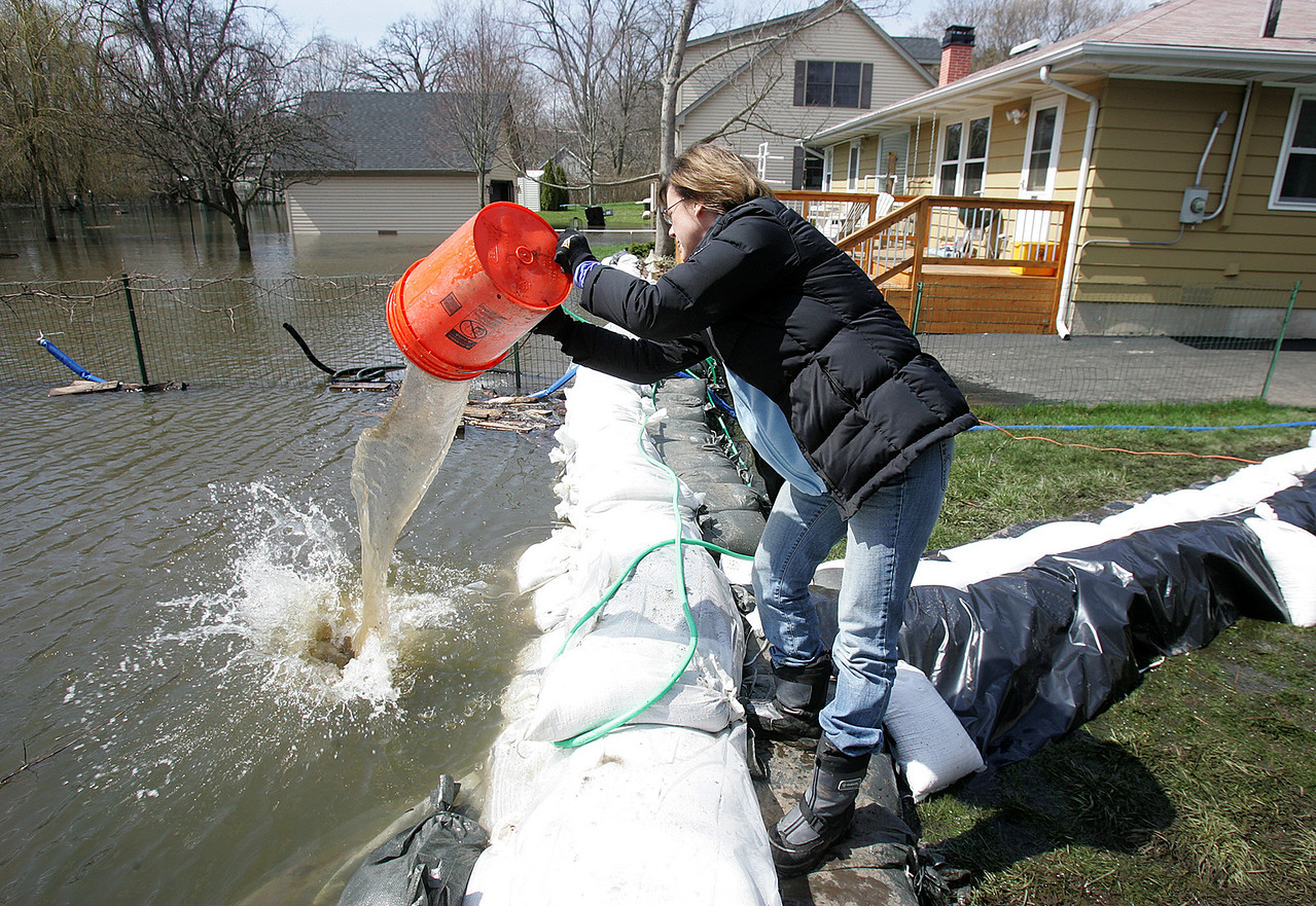 H. Rick Bamman - hbamman@shawmedia.com  Cathy Angarolqa removes river water that seeped under sandbags at her Willow home in Algonquin.