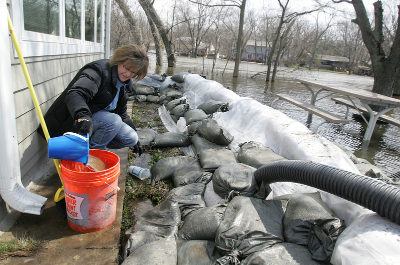 H. Rick Bamman - hbamman@shawmedia.com  Cathy Angarola fills a bucket with river water that seeped under sandbags at her Willow Rd. home in Algonquin. Angarola was working to keep the new carpet in the sun room dry.