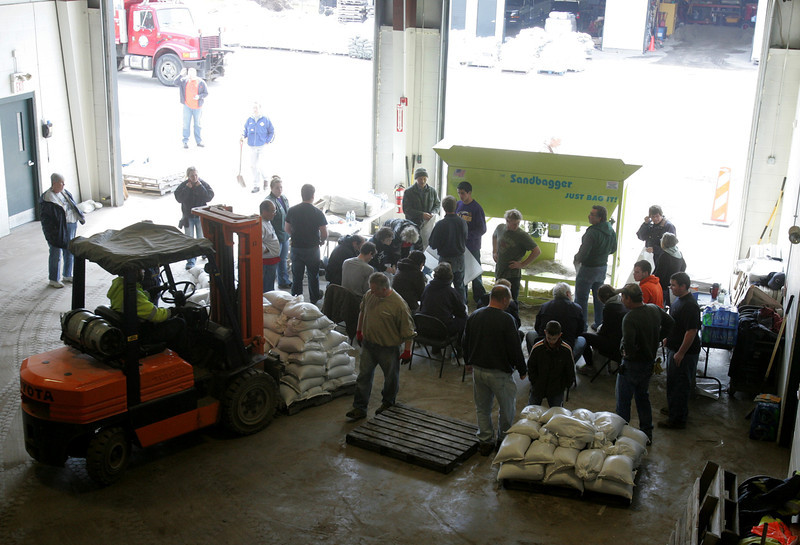 H. Rick Bamman - hbamman@shawmedia.com  Volunteers from around the area work an assembly line to fill sandbags at the Nunda Township garage Sunday.