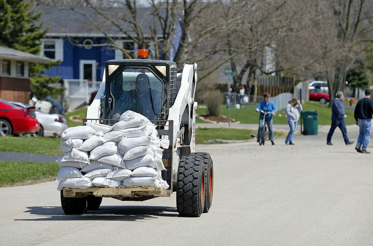 H. Rick Bamman - hbamman@shawmedia.com  Nunda Township employee Al Rosio operates a skid loader on Pine St. in Holliday Hills as residents tried to keep up with flood waters Sunday by sand bagging around their homes.