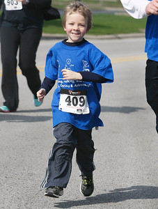 Candace H. Johnson Emerich Parpart, 6, of Wonder Lake is all smiles as he runs during The Human Race, a 5K walk/run supporting McHenry County charities on Corporate Drive in McHenry. Emerich was with his father, Erich, and ran his first race when he was four.