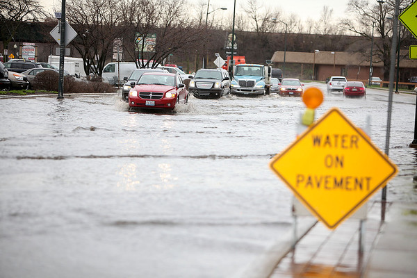 Cars make their way through standing water on Route 31, north of Route 64, in St. Charles Thursday.