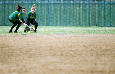 Monica Maschak - mmaschak@shawmedia.com   Crystal Lake South outfielders Sam McLean and Erin Yazel rush for a loose ball during a rainy match against McHenry on Monday, April 15, 2013.  McHenry won 8-1 when officials called the game after the fifth inning.