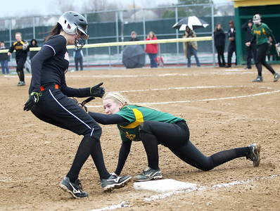 Monica Maschak - mmaschak@shawmedia.com   Crystal Lake South's Lauren Gauger reaches to tag out McHenry's Lindsay Cannon at third base during a rainy match on Monday, April 15, 2013.  The official said Cannon was safe. McHenry won 8-1 when officials called the game after the fifth inning.