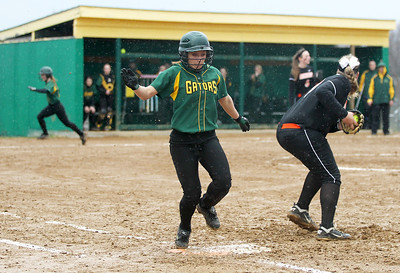 Monica Maschak - mmaschak@shawmedia.com   Crystal Lake South's Kim Woods hit the team's only RBI, but doesn't make it to first base before the ball in the bottom on the fifth inning of a rainy match between McHenry and Crystal Lake South on Monday, April 15, 2013.  McHenry won 8-1 when officials called the game after the fifth inning.