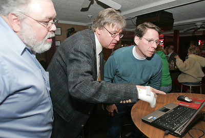H. Rick Bamman - hbamman@shawmedia.com McHenry County College Board of Trustees candidate Chris Jenner of Cary (center) checks election results Tuesday, April 9, 2013 with campaign supporters Lonnie Jarratt (left) and Steve Willson at Kelly's Cuckoo Nest in Cary.