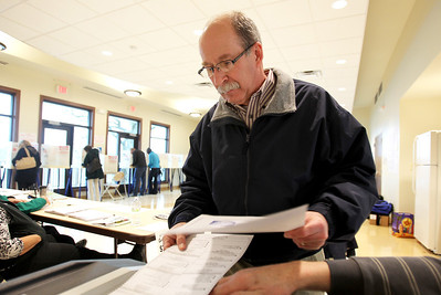 Monica Maschak - mmaschak@shawmedia.com  George Reed, of Crystal Lake, puts his paper ballot into a counting machine for the 2013 general election at the West Beach polling location in Crystal Lake on April 9, 2013.