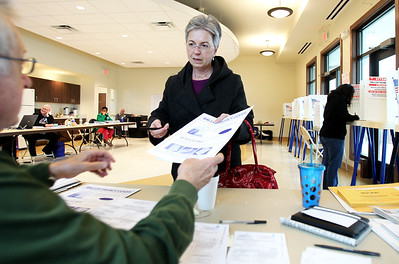 Monica Maschak - mmaschak@shawmedia.com  Rosemary Sanders, of Crystal Lake, receives a voting ballot for the 2013 general election at the West Beach polling location in Crystal Lake on April 9, 2013.