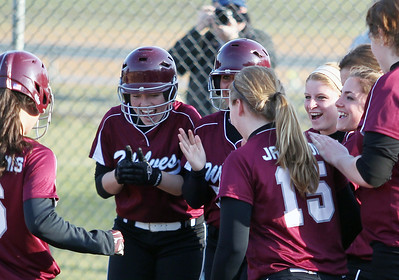 Sarah Nader - snader@shawmedia.com Prairie Ridge's Emily Doomis (center) celebrates with her team after hitting a home run bringing in two runs in the fifth inning of Monday's game against Woodstock North in Crystal Lake on April 8, 2013. Prairie Ridge won, 4-1.