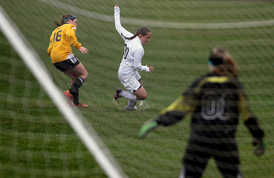Sarah Nader - snader@shawmedia.com Prairie Ridge's Erin ins berg slips in the mud during the first half of Tuesday's rain-shortened soccer game in Crystal Lake on April 23, 2013. Prairie Ridge won, 4-0.