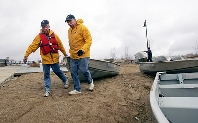 Monica Maschak - mmaschak@shawmedia.com   Albert Roehrig and George Karavites, with the Three Oaks Recreation Area, drag fishing boats to the shore on Friday, April 12, 2013 in preparation for opening weekend of Marina Rentals on Saturday, April 13. Three Oaks will offer row boats with trollingmotors, canoes, kayaks and paddleboats.