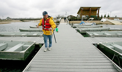Monica Maschak - mmaschak@shawmedia.com   Albert Roehrig, with the Three Oaks Recreation Area, works on docking row boats on Friday, April 12, 2013 in preparation for opening day on Saturday, April 13. Three Oaks will offer row boats with trollingmotors, canoes, kayaks and paddleboats.