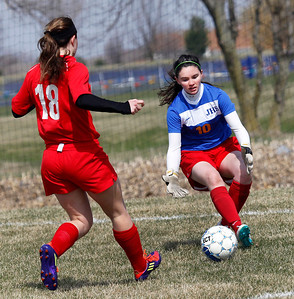 Candace H. Johnson Johnsburg's Amanda Cherwin stops a shot on goal by Mundelein's Aubrey Larkin in the second half during the Lady Hawk Invite at Johnsburg High School. Mundelein won 3-1.