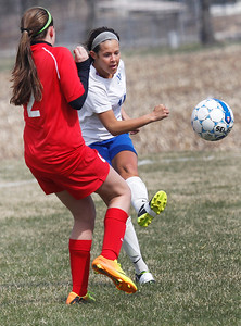 Candace H. Johnson Johnsburg's Delaney Pruitt kicks the ball past Mundelein's Shannon Carroll in the second half during the Lady Hawk Invite at Johnsburg High School. Mundelein won 3-1.