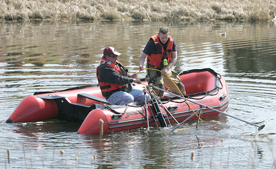 H. Rick Bamman - hbamman@shawmedia.com  Firefighters deploy equipment after a vehicle plunged into a pond at Corporate Drive and Randall Road in Algonquin on Wednesday, April 2, 2014.