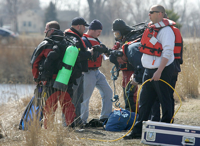 H. Rick Bamman - hbamman@shawmedia.com  Fire department divers stage at the scene after a silver Honda sedan plunged into a pond at Corporate Drive and Randall Road in Algonquin on Wednesday, April 2, 2014.