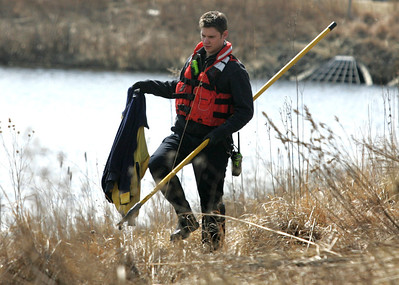 H. Rick Bamman - hbamman@shawmedia.com  A firefighter recovered a jacket after a car plunged into a pond at Corporate Drive and Randall Road in Algonquin on Wednesday, April 2, 2014.