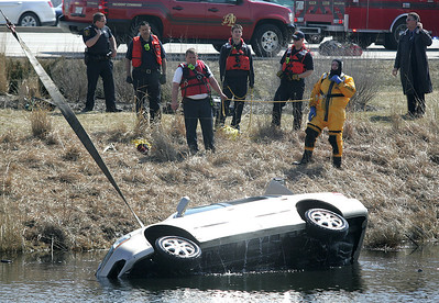 H. Rick Bamman - hbamman@shawmedia.com  A silver Honda sedan is pulled from a pond at Corporate Drive and Randall Road in Algonquin on Wednesday, April 2, 2014. The driver was rescued through the sun roof as the car began to sink.