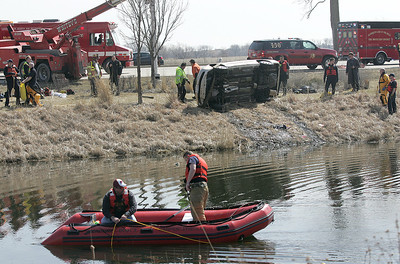 H. Rick Bamman - hbamman@shawmedia.com  Fire department crews retrieve equipment after a Honda sedan plunged into a pond at Corporate Drive and Randall Road in Algonquin on Wednesday, April 2, 2014. The driver was rescued through the sun roof as the car began to sink.
