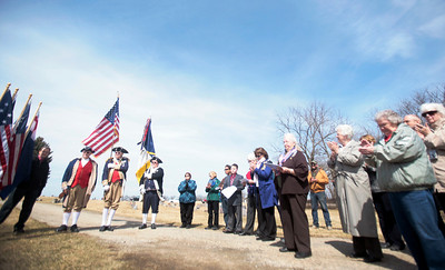 Michelle LaVigne/ For Shaw Media The color guard wearing Revolutionary War-period appropriate uniforms march out in the center of a gathering for the dedication of a plaque honoring and describing the life of Revolutionary War soldier Major Watson, inside of Linn-Hebron Cemetery in Hebron, Ill., on April 6th, 2014. The Sons of the American Revolution is seeing to it that graveyards across Illinois are marked with a plaque showing they have a Revolutionary Patriot buried inside.