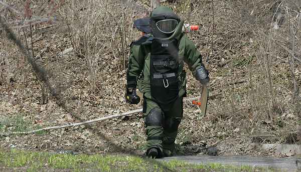 H. Rick Bamman - hbamman@shawmedia.com  A Kane County Sheriff's bomb and arson squad technician returns to the staging area after examining a green piece of PVC pipe found in the wooded area just south of Algonquin Rd. on Tuesday, April 8, 2014.