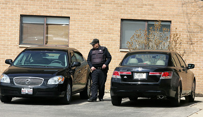 H. Rick Bamman - hbamman@shawmedia.com  An Algonquin police officer returns to his patrol car after alerting residents of an apartment building to the incident.
