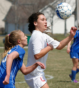 John Konstantaras-for Shaw Media Woodstock's Lizzy Kruse (16, left) and Mundelein's Michele Chernesky (3) work for position on a ball during the first half of their game during the Johnsburg Soccer Tournament at the Hiller Park Field Friday, April 18, 2014.