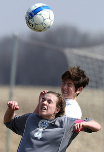 John Konstantaras-for Shaw Media Johnsburg's Shaylah Pegues (behind) and Woodstock's Kristen Schreiner (4) fight for a header during the second half of their game during the Johnsburg Soccer Tournament at Johnsburg High School Friday, April 18, 2014. The Blue Streaks won the game 3-2.