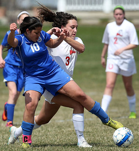 John Konstantaras-for Shaw Media Woodstock's Leiana Haanio(10) reaches across Mundelein's Michele Chernesky (3) for a ball during the first half of their game against Mundelein during the Johnsburg Soccer Tournament at the Hiller Park Field Friday, April 18, 2014.