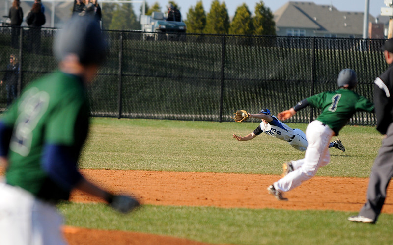 St. Charles North's Nick Drawant lays all out for a diving catch during his team's 3-2 come-from-behind victory over Bartlett on Friday, April 18, 2014 on the North Stars home field.