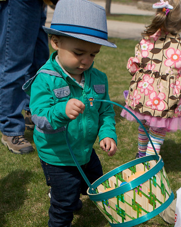 Karen Naess For The Kane County Chronicle<br /> Spencer Clanton 2 years old from Batavia fills his basket  during the first ever Batavia Easter egg hunt on Saturday.